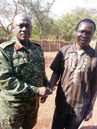 Former military police commander Colonel Kabango shaking Ongwen's hand minutes after he was handed over to the UPDF by US forces